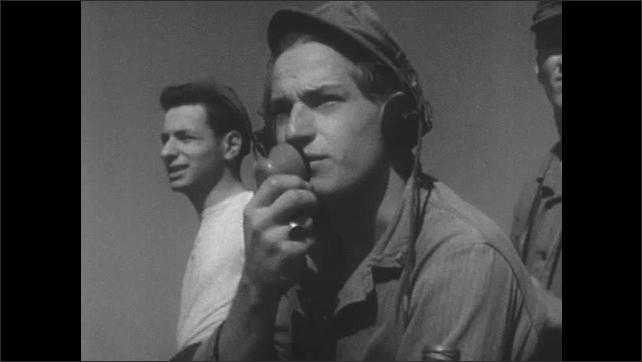 1960s: UNITED STATES: plane over ground. Man speaks on radio. Man writes notes on airfield