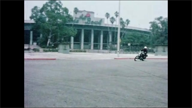 1960s: Tracking shot, motorcycle driving on street. Pan of motorcycle going around curve. Tracking shot of motorcycle driving.