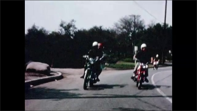 1960s: Long shot, motorcycle drives down road. Motorcycle goes around curve. Tracking shot, group of motorcycles on road.