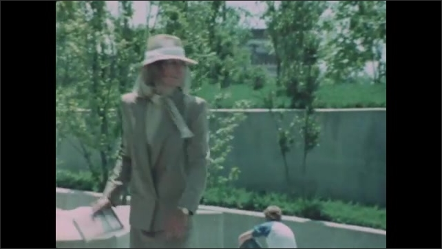 1980s: Woman runs up steps and looks around suspiciously then begins walking while reading book and looking around.