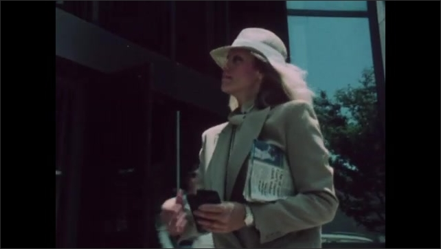 1980s: Picture of two women in wallet. Woman closes wallet while walking down street. Woman walks down city street holding newspaper under arm.