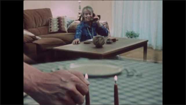 1980s: Woman sits on floor by coffee table and talks on telephone. Hand light's candles on dining table.