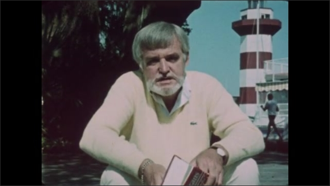 1980s: Man sits on ground near lighthouse and speaks. Text on screen. Man stands and holds book. Man speaks.