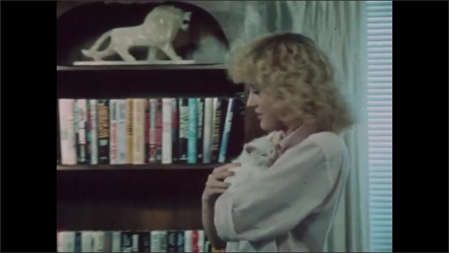 1980s: Man with headphones squeezes hand exerciser and reads book. Woman carries cat to bookshelf and removes novel. Cat looks at book in woman's hand.