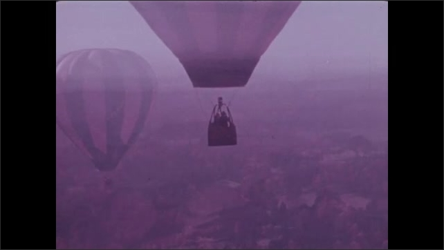 1970s: Two men in hot air balloon drift over North Carolina. Man in leisure suit adjusts the burner.