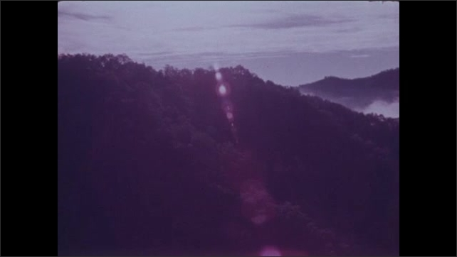 1970s: Aerial view of fog and clouds over forested hills.