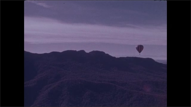 1970s: Hot air balloon floats over forest with autumn color changing leaves.
