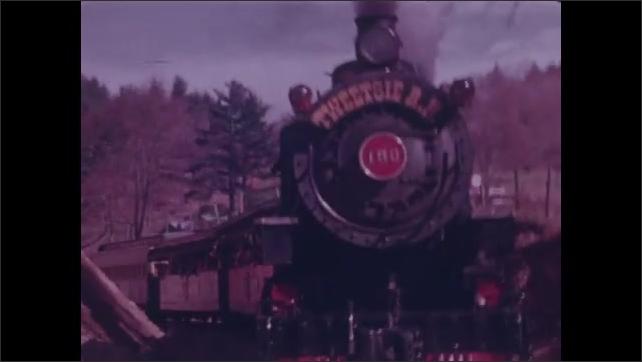 1970s: Steam train on railroad tracks. Tweetsie Railroad engine chugs down tracks. Two men playing train robbers pretend shoot at train.