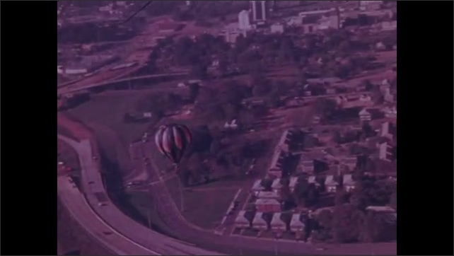 1970s: Woman in colonial costume waves from Old Salem building near Winston-Salem. Hot air balloon drifts over the city of Charlotte.