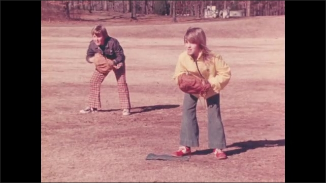 1970s: Boys and girls pound mitts and play baseball on playground. Boys and girls jump and cheer on players.