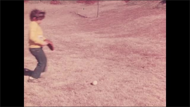 1970s: Girl catches ground ball and throws to boy. Boy misses baseball and chases after it. Boy looks across field and throws baseball.