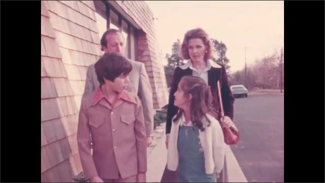 1970s: Boys and girls play with toy guns. Family walks up sidewalk and talks. Family enters building.