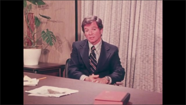 1970s: Man sits at desk in office and speaks. Girl looks down as children play together at recess.