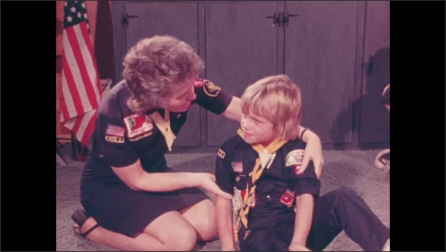 1970s: Cub scouts wrestle on floor in den. Den mother pulls aggressive boy away and talks to him.