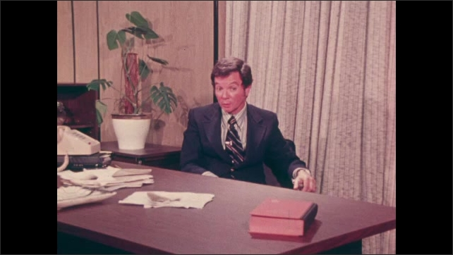 1970s: Man looks over newspaper and speaks. Man sits at desk in office and speaks. Man sits on sofa and talks to boy.