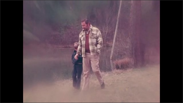 1970s: UNITED STATES: man walks outdoors with young boy. Boy holds father's hand on walk.  Man in bed with illness.