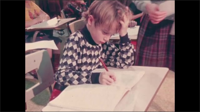 1970s: UNITED STATES: close up of boy's face. Boy works at desk. Teacher talks to student at desk.