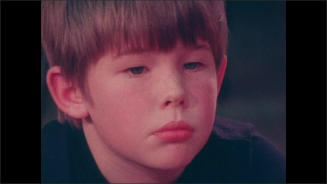 1970s: UNITED STATES: child looks sad in class. Boy cries.
