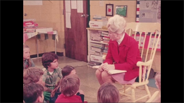 1970s: UNITED STATES: boy asks teacher a question. Teacher answers questions in classroom
