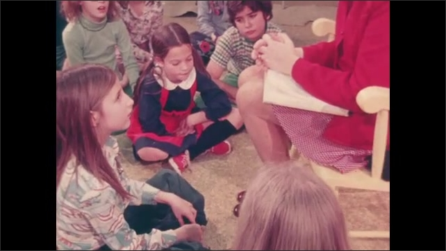 1970s: UNITED STATES: girl asks teacher a question. Teacher answers questions in class. Students sit on ground in lesson.