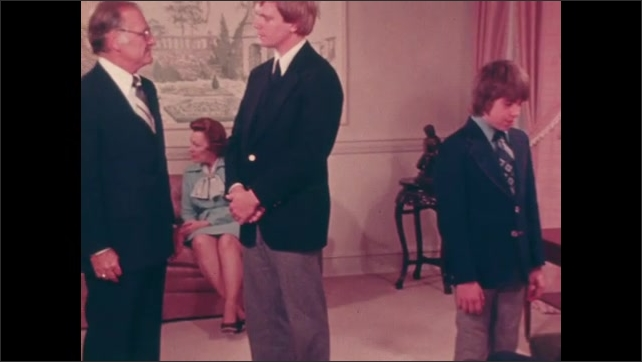 1970s: UNITED STATES: wooden coffin on stand at wake. People attend funeral. Men shake hands. Visitors in state room. Man talks to boy at funeral.