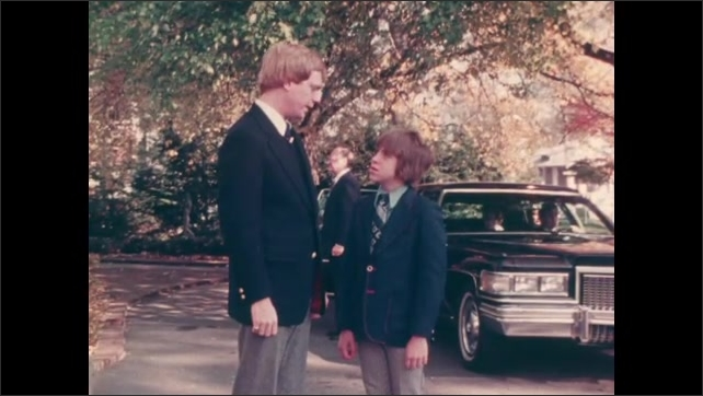 1970s: UNITED STATES: close up of boy's face. Man talks to boy at funeral. Funeral cars parked by home. Father and son attend funeral