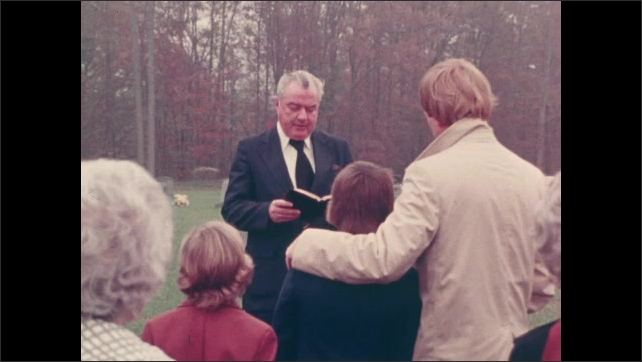 1970s: UNITED STATES: man reads from Bible at funeral. Family attend funeral at cemetery