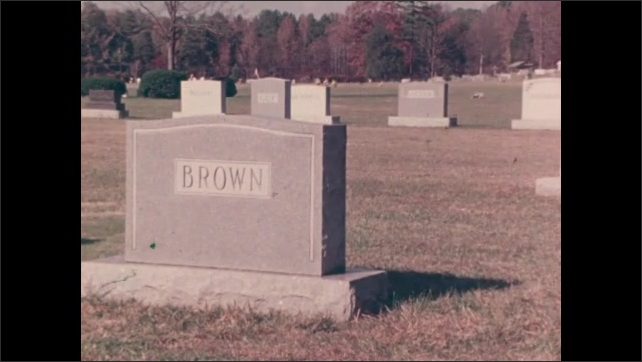 1970s: UNITED STATES: graves in cemetery. Father and son lay flowers at grave.
