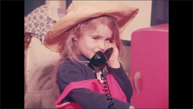 1970s: UNITED STATES: boy talks with friends. Children in play area. Girl in costume talks on play phone.