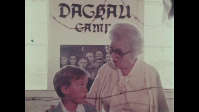 Older woman stands next to young blonde boy in front of a Dachau exhibit poster. Woman puts arm around boy and speaks.