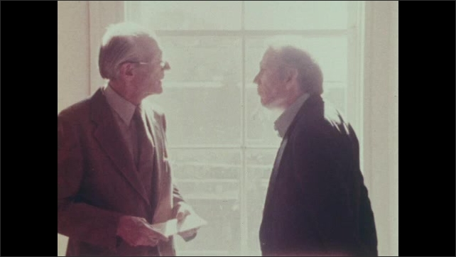 Two older men walk through the Concentration Camp museum and talk animatedly. One man turns toward the sun-filled window and looks outside.