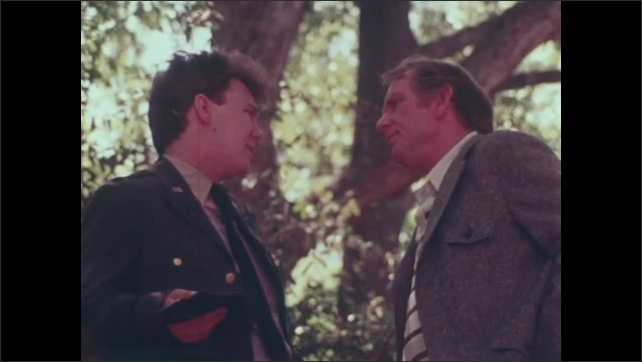 1980s: UNITED STATES: men talk on bridge in woods. Man in uniform talks to father. View of men talking through trees. Close up of man's face. Man leans over bridge