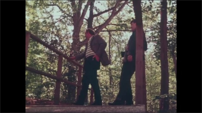 1980s: UNITED STATES: close up of man's face. Men talk in woods. Father talks to son on walk. View of men through trees.