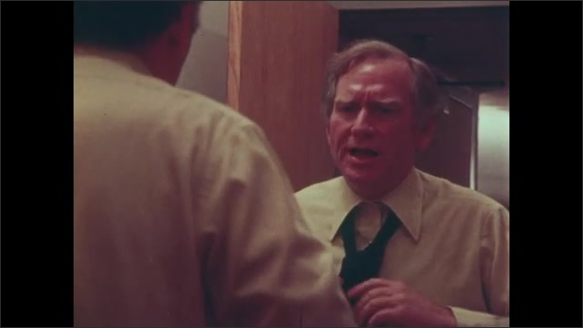1980s: UNITED STATES: lady talks with husband at home. Man puts on shirt. Man does tie in mirror. Man talks to self in mirror.