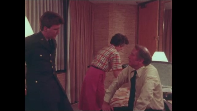 1980s: UNITED STATES: son kisses mother at door. Man in military uniform visits parents. Lady takes photo of son in uniform. Man gives leaflet to son.