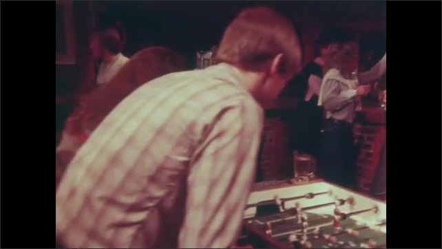 1980s: UNITED STATES: Lady serves beers at party. Men play on football table. Oktoberfest style party. People dance at party