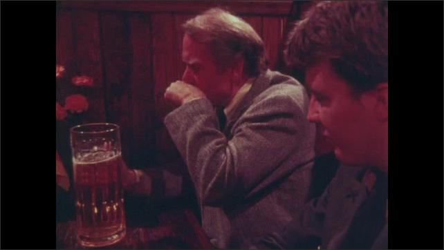 1980s: UNITED STATES: men talk at table in bar. Men knock glasses. Man in uniform Men drink beer.