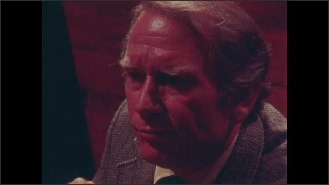 1980s: Men sit at table in restaurant, talk.