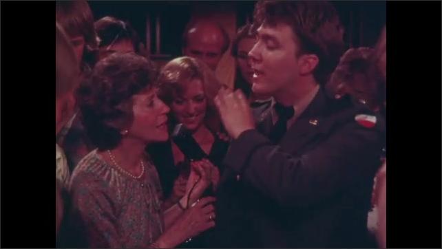 1980s: Woman talks to man in crowd of people. Men play foosball.