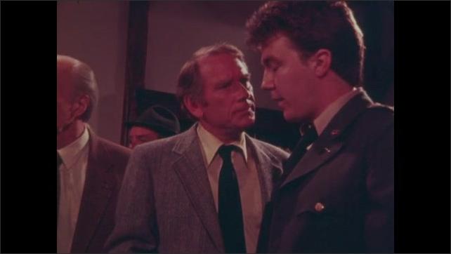 1980s: Men argue in bar.