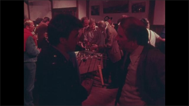 1980s: Man in suit and man in uniform walk away from foosball table, have conversation.