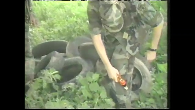 1990s: Heap of tires. Stacks of tires. Person scrapes bottom of foot on tire. Man in army fatigues uses small vacuum to suck mosquitos off man's arm.