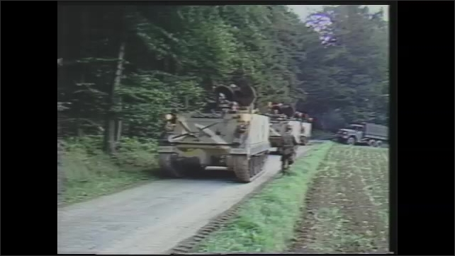 1980s: Tank in muddy ditch.  Wrecked truck.  Broken window.  Vehicles roll down road and through woods.  Man gestures.  Tanks are loaded onto transport vehicle.