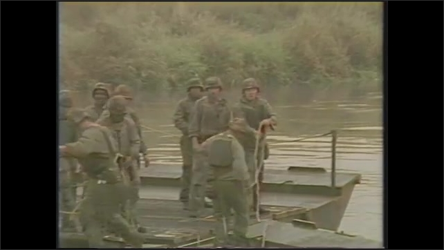1980s: Commanding officer speaks to soldiers.  Boat is launched from back of truck.  Men throw ropes and tie barges together.