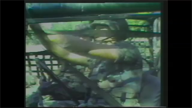 1980s: Tank and trucks drive on highway in convoy.  Soldier fastens seat belt.  Soldiers pull down tailgate of truck.  Soldiers get out of truck.