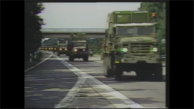 1980s: Traffic on highway.  Military convoy.  Rainy night.