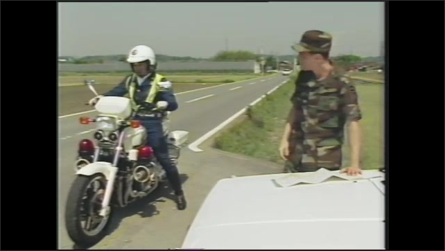1990s: US Army soldier stands on the side of the road looking at a map. Soldier waves down a Japanese motorcycle policeman. Motorcycle policeman looks at map on hood of car.
