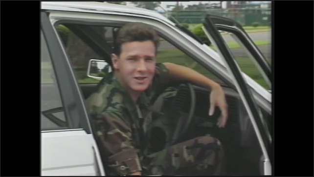 1990s: U.S. soldier sits in a Japanese car with the steering wheel on the right hand side and turns on the windshield wiper instead of a turn signal. Soldier closes the car door and drives off.