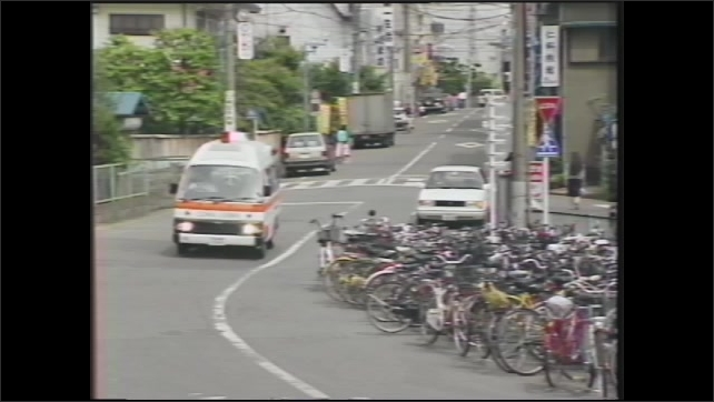 1990s: U.S. soldier is driving on a busy Japanese road and must pull over to the left to give way for an ambulance.