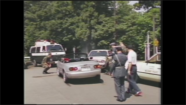 1990s: Convertible car smokes and is stopped after an accident. U.S. soldier examines the damaged car. U.S. Army police and Japanese police make a report.